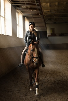 Indoor photo of young woman jockey riding horse on manege