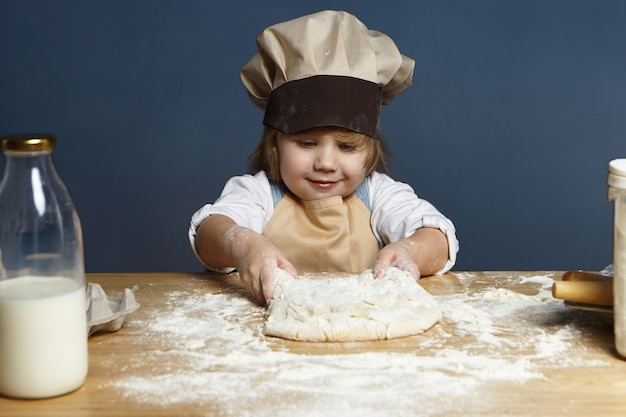 Indoor picture of beautiful cheerful european little girl in chef headwear and apron kneading dough at kitchen table, making bread or cake. pastry, cooking, bakery, baking and preparing concept