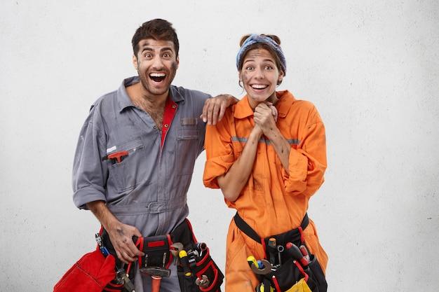 職場で宣伝されているように興奮している感情的な女性と男性の配管工の屋内写真