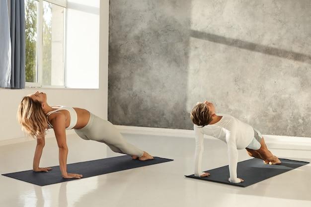 Фотография в помещении: подтянутая блондинка и мускулистый мужчина вместе практикуют асаны йоги в современном тренажерном зале, делают планку назад, чтобы получить сильные руки и торс. концепция здорового образа жизни, активности и спорта