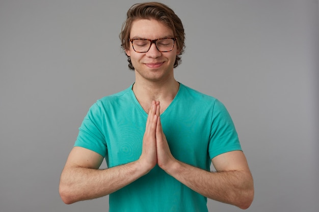 Indoor poratrait of young joyful positive male, keeps his eyes closed and palms together in praying position, smiling while think about future. isolated over gray background