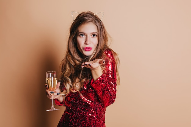 Indoor portrait of adorable european woman in red dress sending air kiss and holding glass of champagne