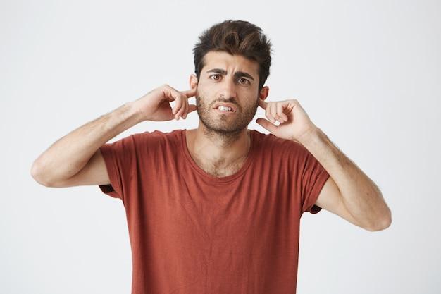 Ritratto dell'interno del tipo maturo spagnolo arrabbiato che indossa maglietta rossa che sembra arrabbiata e che ostruisce le orecchie con le dita nella discussione con l'amica.