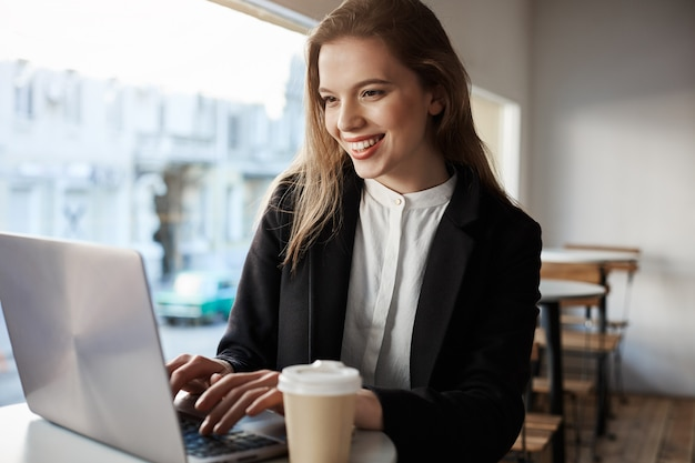 Indoor portrait of attractive european woman sitting in cafe, drinking coffee and typing in laptop, being happy and pleased.