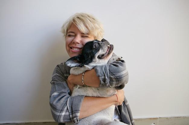 Ritratto dell'interno di giovane femmina felice attraente che dà abbraccio amorevole al bulldog francese bianco e nero, indossando abiti casual, concetto di emozioni positive