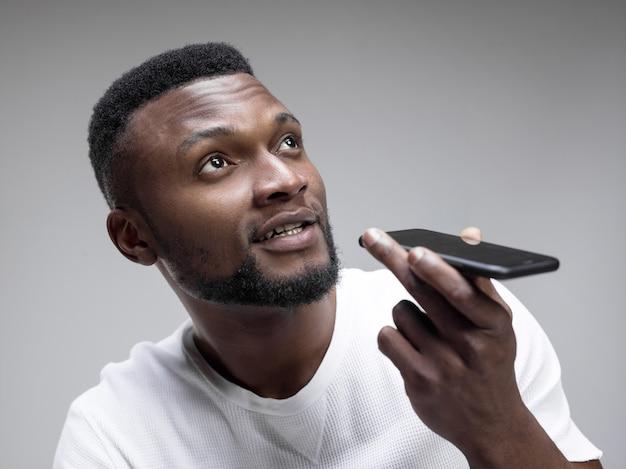 Indoor portrait of attractive young black man holding blank smartphone