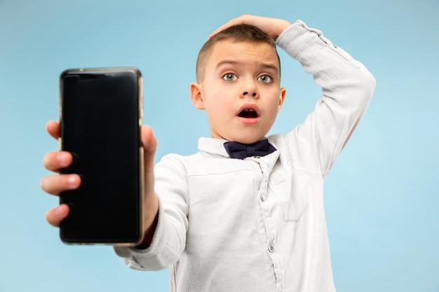 Ritratto dell'interno del giovane ragazzo attraente che tiene smartphone in bianco
