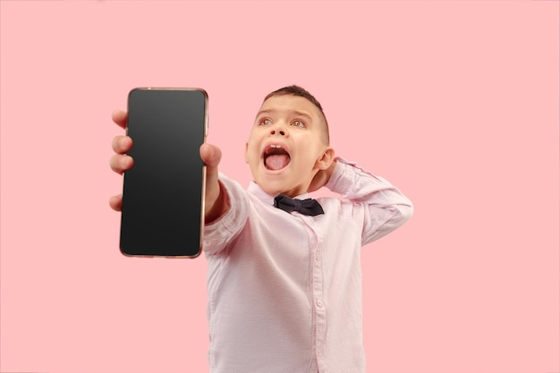 Indoor portrait of attractive young boy holding blank smartphone