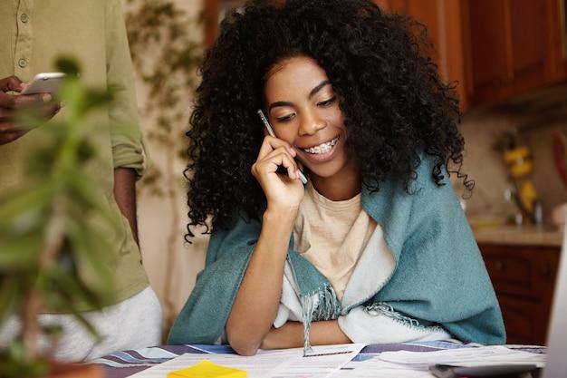Ritratto dell'interno di attraente giovane femmina dalla carnagione scura con l'acconciatura riccia che ha conversazione telefonica