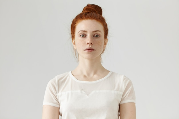 Indoor portrait of attractive young european ginger woman with freckled face and hair bun dressed in white blouse, her look and posture expressing self-confidence