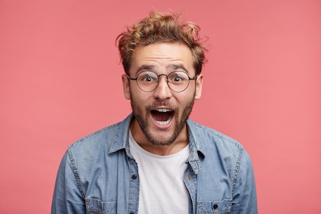 Indoor portrait of bearded young man with trendy hairstyle