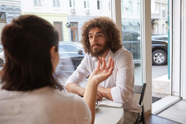 Indoor portrait of beautiful curly male with beard having meeting in cafe, looking attentively and calmly on female next to him, sitting at table by the window