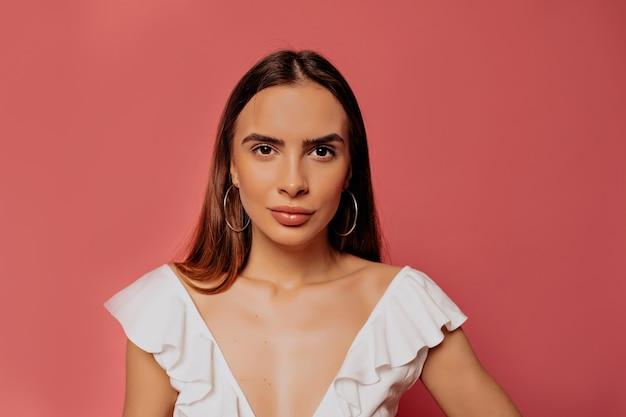 Ritratto al coperto di bella donna graziosa che indossa la maglietta bianca in posa durante il servizio fotografico sul muro rosa