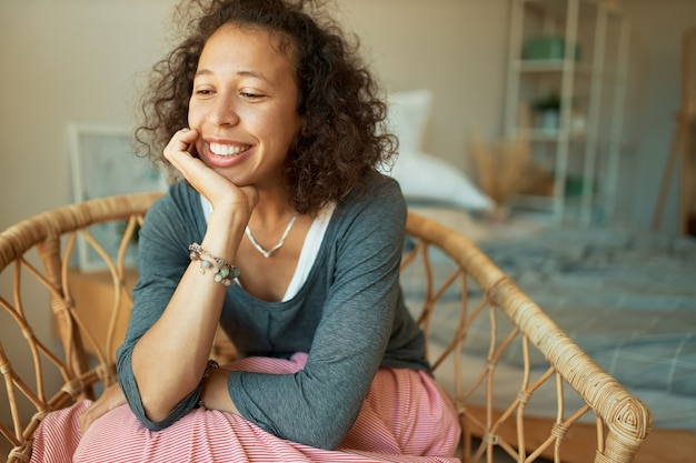 Indoor portrait of beautiful shy young hispanic woman with dark skin and long curly hair relaxing at home, sitting in rattan chair smiling broadly