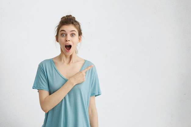 Indoor portrait of beautiful woman with hair knot wearing casual t-shirt having eyes popped out and mouth dropped pointing with finger at copyspace