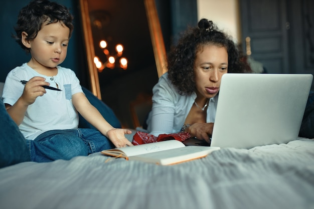 Indoor portrait of beautiful young female freelancer working remotely from home lying on bed with laptop while her cute little son holding pencil