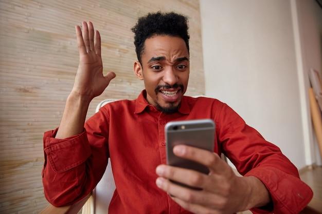 Ritratto dell'interno di sconcertato giovane maschio dalla pelle scura barbuto guardando eccitato lo schermo del suo telefono cellulare e tenendo la mano alzata, isolato sull'interno domestico