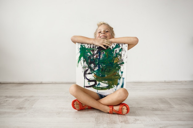 Indoor portrait of blonde smiling with her teeth little girl sitiing cross-legged on the floor, hugging picture she painted for her parents. happy female child being proud of herself. people and posit