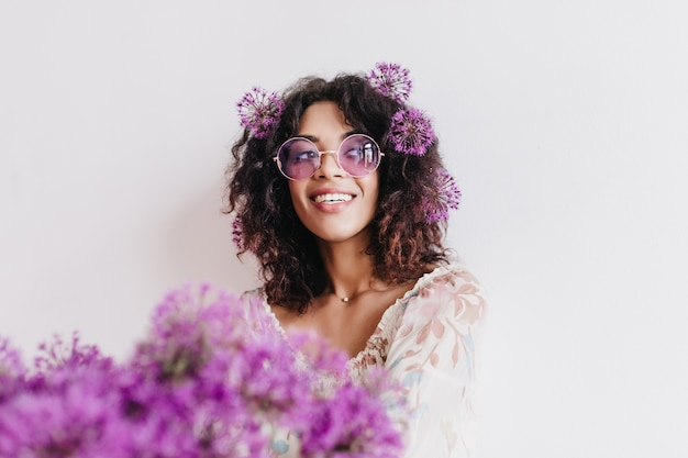 Indoor portrait of carefree black girl looking away during photoshoot with flowers. pleased african lady expressing interest while posing with alliums.