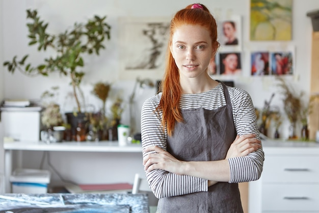 Indoor portrait of charming confident young redhead crafts woman wearing grey apron standing in her workshop, keeping her hands crossed and smiling, ready for process of creation and hard work