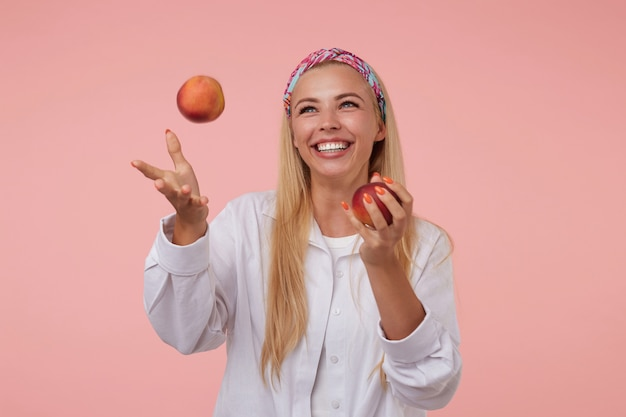 Indoor portrait of charming young blonde woman wearing white shirt, smiling widely and throwing up peaches, standing