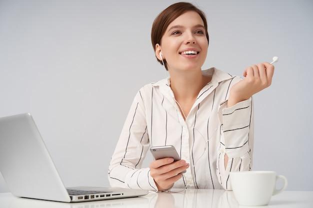 Ritratto dell'interno di affascinante giovane donna castana con taglio di capelli corto alla moda che osserva da parte con un sorriso positivo e che tiene l'auricolare in mano alzata, posa su bianco in eleganti abiti formali