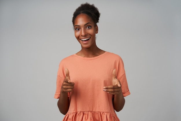 Ritratto dell'interno di affascinante giovane donna riccia dalla pelle scura che punta felicemente con gli indici sollevati e sorridente ampiamente, isolato su grigio