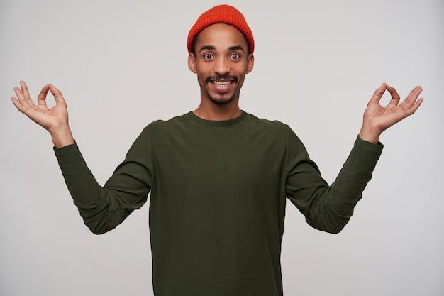 Ritratto dell'interno di allegro giovane uomo dalla pelle scura dagli occhi marroni con la barba che sorride ampiamente e che solleva le mani con il segno di mudra, isolato su bianco