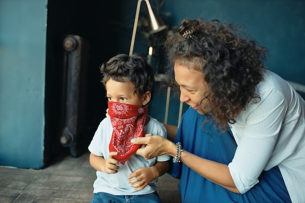 Indoor portrait of cheerful young latin woman in casual clothes sitting on floor with her adorable cute little son