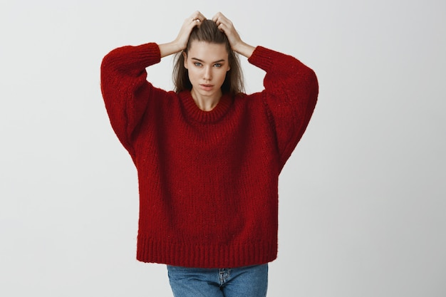 Indoor portrait of confident attractive caucasian businesswoman in stylish red sweater, touching hair and looking focused , posing sensually  for advertisement
