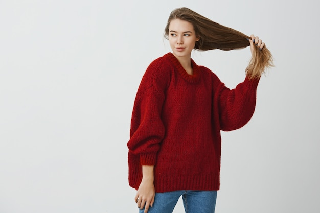 Indoor portrait of curious romantic caucasian woman in loose red sweater, holding beautiful healthy hair in hand aside, looking left with passionate relaxed mood, standing