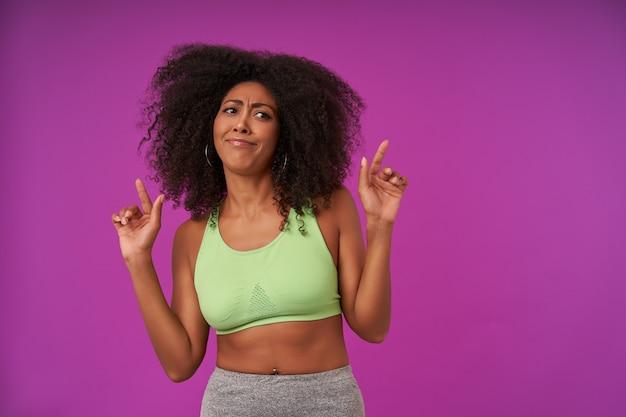 Ritratto interno di donna dalla pelle scura con capelli ricci che fa smorfie sul viola, indossa abiti sportivi, alzando le mani con gli indici che mostrano verso l'alto, guardando da parte e accigliato