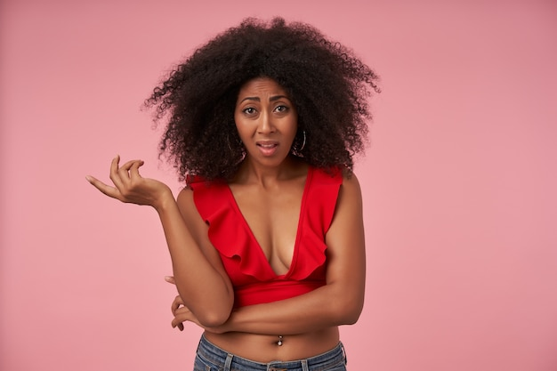 Indoor portrait of dark skinned woman with belly button piercing standing on pink with confused face and frowning with raised palm