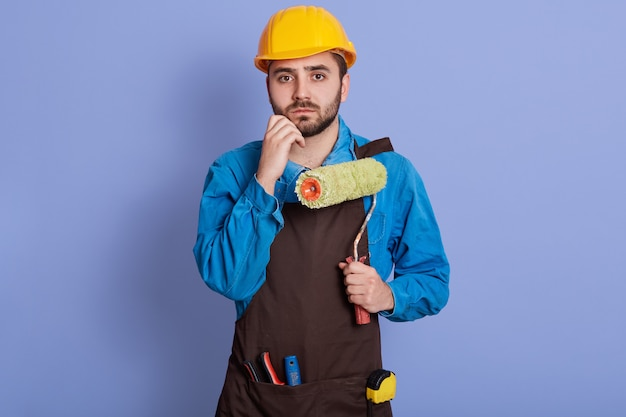 Indoor portrait of disappointed confused young builder putting hand to chin, holding roller, having thoughtful facial expression, wearing uniform and helmet, posing isolated over lilac wall.