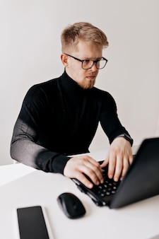 Indoor portrait of european young man wearing black pullover and spectacles working with laptop in the light office in sunny day.