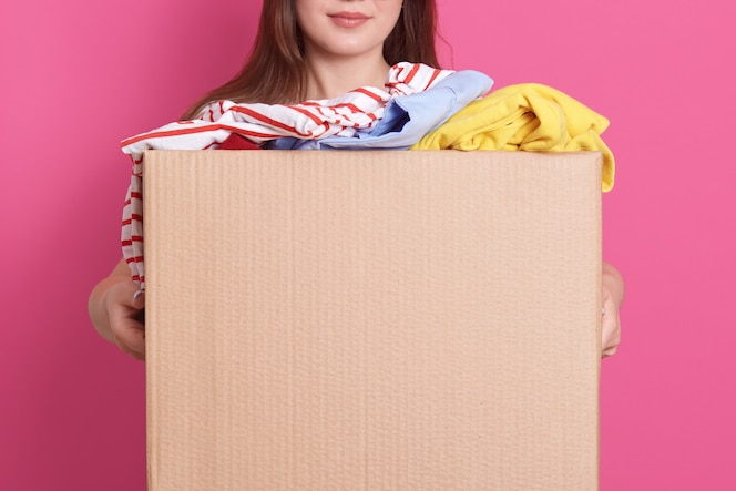 Indoor portrait of faceless girl standing with cardboard box in hands, holding carton box full of fashionable clothes isolated on rosy wall. Donation, charity and volunteering concept.