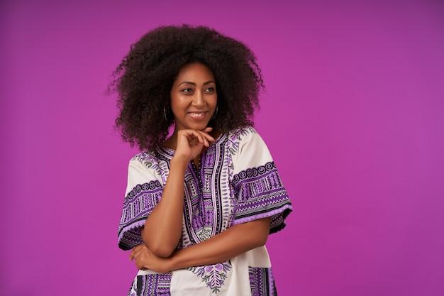 Ritratto al coperto di flirty donna dalla pelle scura con acconciatura casual che indossa camicia fantasia bianca, guardando da parte con un sorriso affascinante e mento pendente sulla mano sollevata, isolato su viola