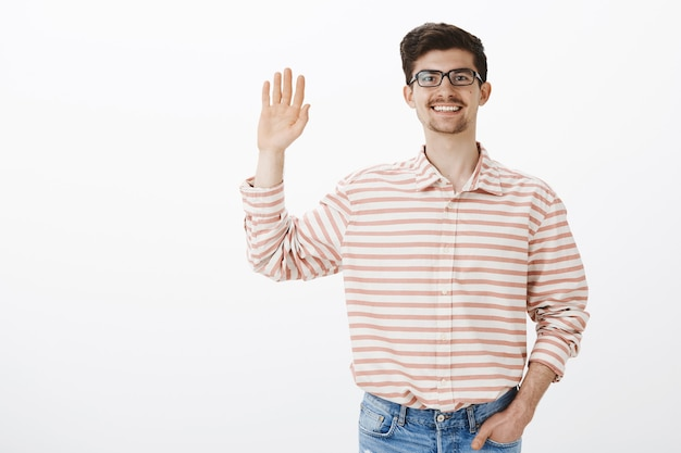 Indoor portrait of friendly ordinary european guy with beard and moustache in nerdy glasses, raising palm and waving, saying hi to team members, greeting staff