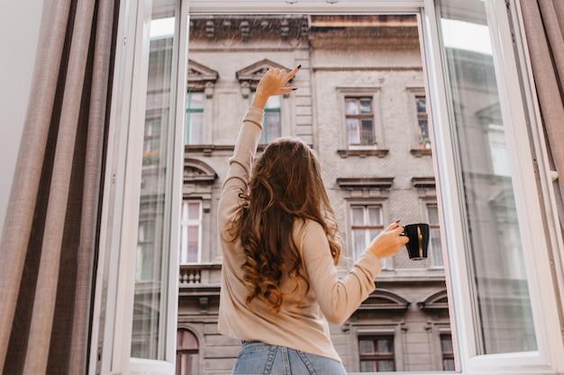 Портрет в помещении со спины стройной девушки с длинными вьющимися волосами в джинсах