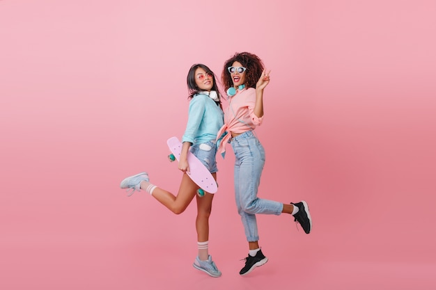 Indoor portrait of funny girls dancing with pink interior. sporty mulatto lady in blue jeans having fun with best friend holding longboard.