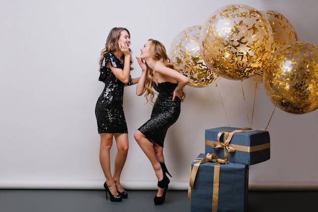 Indoor portrait of glamorous blonde girl funny posing next to present packages. stunning caucasian woman in trendy black dress enjoying birthday party with fair-haired friend.