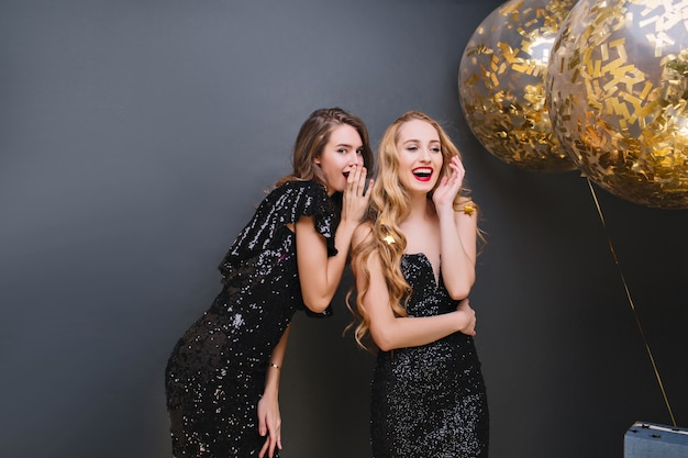 Indoor portrait of glamorous girls sharing rumors during party. stunning ladies in black dresses talking about secrets while celebrating something with balloons.