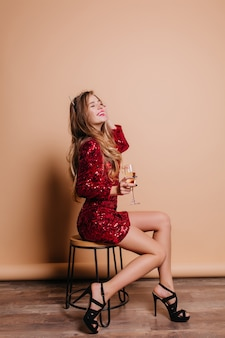 Indoor portrait of glamorous woman in black sandals and party dress sitting on chair on beige wall
