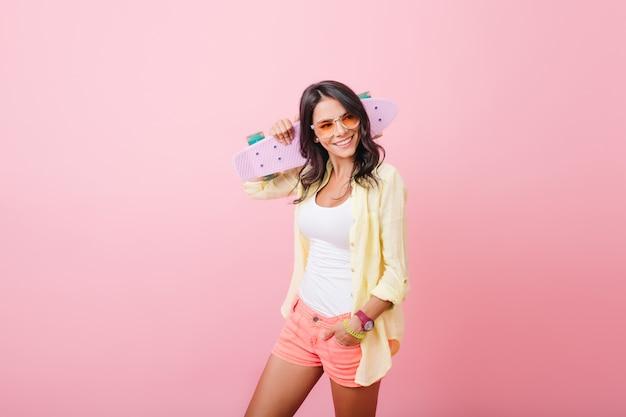 Ritratto dell'interno della splendida ragazza latina in occhiali da sole in posa. fiduciosa giovane donna in camicia gialla divertendosi, tenendo lo skateboard.