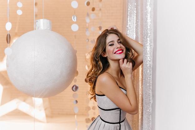 Ritratto dell'interno della donna splendida con l'umore festivo e di capodanno in abito luminoso ed elegante. la bruna riccia sorride ampiamente