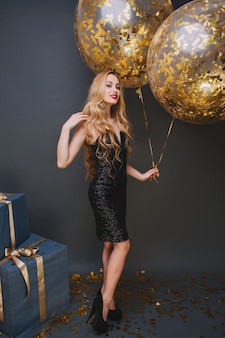 Indoor portrait of graceful curly lady posing with pleasure at her birthday party. glad female model in sparkle black dress standing near balloons and present boxes during event.