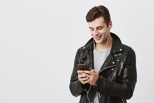 Indoor portrait of handsome caucasian guy in trende leather jacket holding mobile phone, messaging with his friends, telling them about his journey abroad having pleasant smile