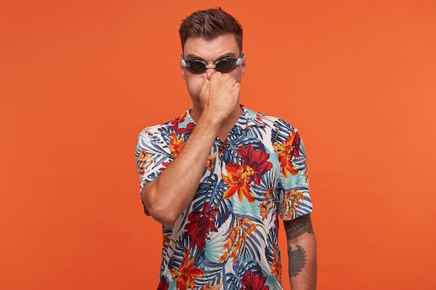 Indoor portrait of handsome young guy wearing swimming glasses and flowered shirt, closing nostrils with hand and training to hold breath, standing