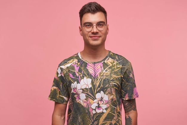 Indoor portrait of handsome young guy with tattoos wearing glasses and flowered t-shirt, smiling gently, isolated