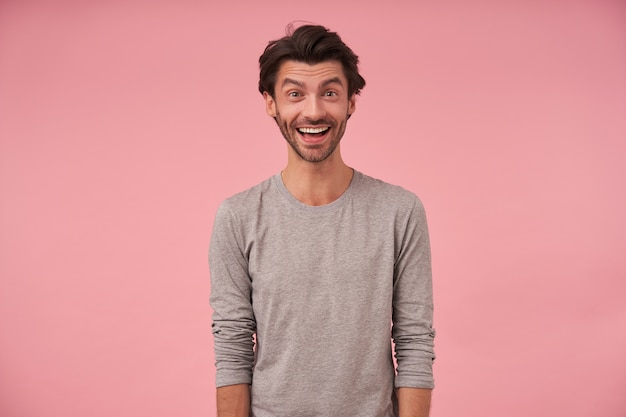 Indoor portrait of happy bearded male with trendy haircut wearing casual clothes, posing with hands down, looking cheerfully with wide mouth opened
